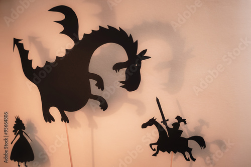Plakat Shadow Puppets of Dragon, Princess and Knight z jasnym świecącym ekranem teatru cieni w tle.