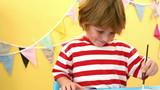 Happy boy using a paint brush