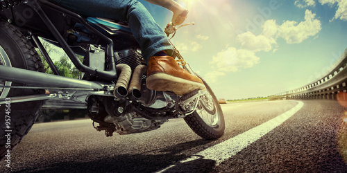 Biker riding motorcycle on an empty road at sunset Poster