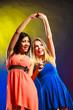 Obrazy na płótnie, fototapety, zdjęcia, fotoobrazy drukowane : Two funny women holding hands in dresses.