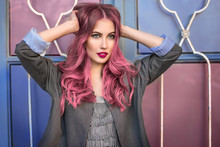 Piękny model hipster mody z kręcone różowe włosy stwarzających z przodu kolorowe ściany