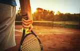 Fototapety Man holding tennis racket/Close up of man holding tennis racket on clay court. In his hand is tennis ball. On court is sunset.