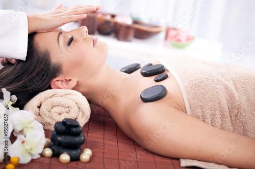 Beautiful woman having a wellness head massage at spa salon