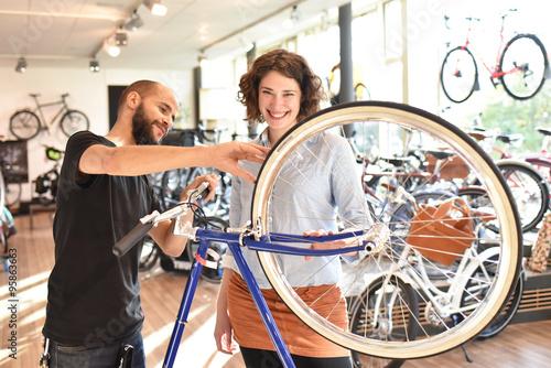 Poster sales in the bicycle shop // Kundin mit Verkäufer in einem Fahrradgeschäft