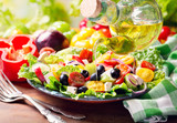 olive oil pouring into plate of greek salad - 95910215