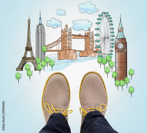 Top view of the casual man's brown shoes and drawn sketches of the most popular cities in the world. The concept of travelling. London, Singapore, Pisa, Paris. Light blue background. © denisismagilov