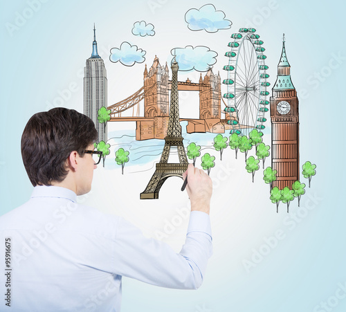 A handsome young man is drawing a colourful sketches of the most popular cities in the world. The concept of travelling. London, Singapore, Pisa, Paris. Light blue background. © denisismagilov