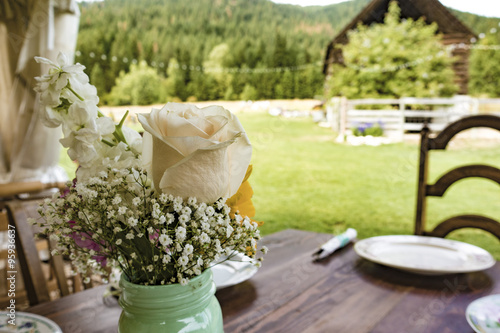 Wedding Table Settings With Flowers, Utensils, Chairs and Dishes