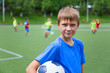 Boy footballer with a ball on soccer field