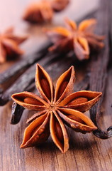 Closeup of star anise and fragrant vanilla on wooden surface plank