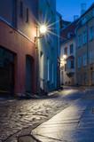 Fototapety Illuminated narrow street at night in Tallinn Old Town, Estonia