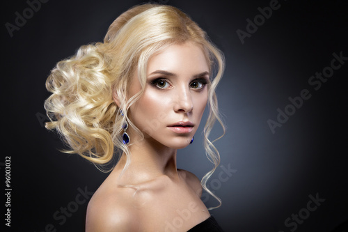 Poster Beautiful blond girl in a black dress with evening haircut  form of waves and bright makeup