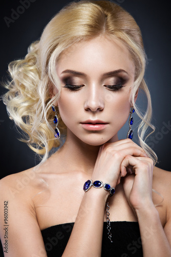 Tela Beautiful blond girl in a black dress with evening haircut  form of waves and bright makeup