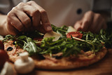 Woman cook pizza with arugula, parmesan and vegetables on wood table in the kitchen.