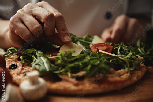Fotobehang Pizzeria Woman cook pizza with arugula, parmesan and vegetables on wood table in the kitchen.