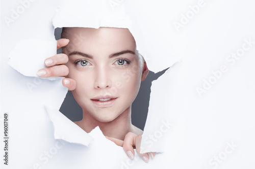 woman looking out from behind a hole in a paper sheet