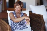 Anziana e vitale signora in vacanza applica filtro solare prima di lasciare l