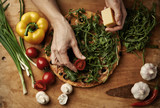 Top view of delicious and healthy pizza lying on wooden board with cherry tomatoes, mushrooms, onion, pepper, greens.