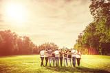 skupina dospívajícími přáteli v parku při západu slunce