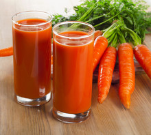glasses of carrot juice and carrots on a wooden table
