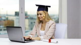 student in bachelor cap with laptop and diploma