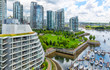 Vancouver aerial view of of glass towers and waterfront park along a marina with boats