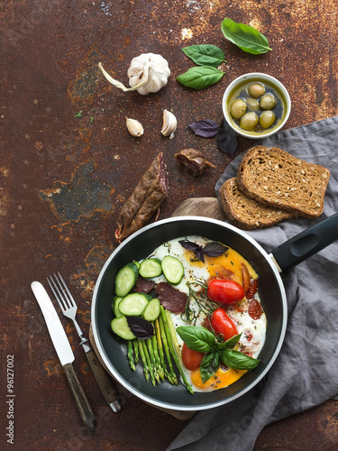 Foto: Pan of fried eggs, salami, asparagus, cherry-tomatoes with bread ...