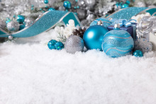 Christmas border with decorations and gift on the snow. Space for copy.