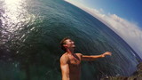 POV Slow Motion Cliff Jumping Backflip. Athletic Young Man Jumping From Cliff Into Ocean.