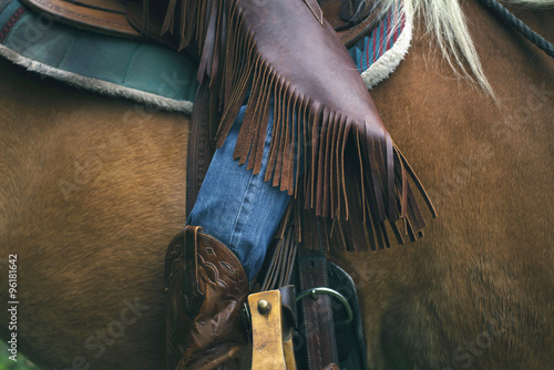 Close-up of western style horse chaps while sitting on horse. Poster