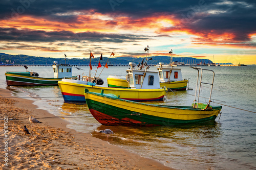 Picturesque landscape of a sunset with a boats on beach in Sopot, Poland.