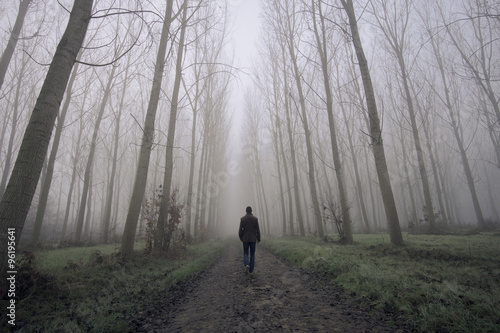 Man walking on a dirty road between fog and trees