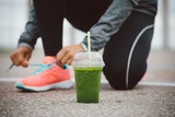 Fototapety Detox smoothie drink and running footwear close up. City outdoor workout and fitness healthy nutrition concept.  Female athlete tying sport shoes laces before training.