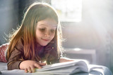 Cute Girl Reading a Book at Home