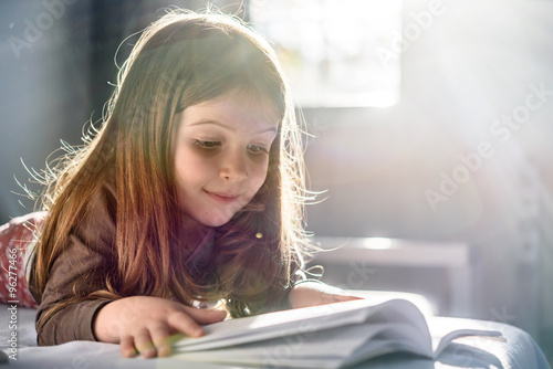 Fotografiet Cute Girl Reading a Book at Home