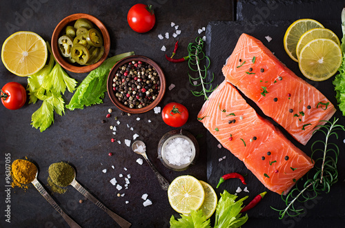 Fototapety, obrazy : Raw salmon fillet and ingredients for cooking on a dark background in a rustic style. Top view
