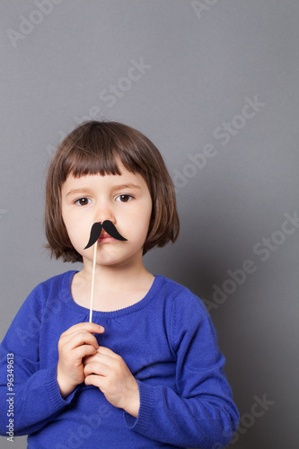 Poster kid moustache concept - fun 4-year old Charlie Chaplin look alike dressing up wi