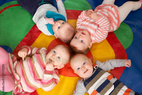 obraz PCV Overhead View Of Babies Lying On Mat At Playgroup