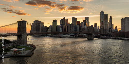 Lower Manhattan and Financial District skyline at sunset with the Brooklyn Bridge over the East River. Silhouettes of skyscrapers catch the last last of the daylight. New York City