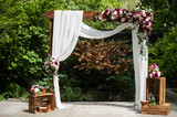 Wedding arch decorated with cloth and vivid flowers - 96386026