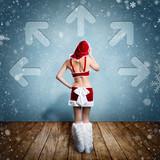 attraktive Weihnachtsfrau steht vor Wand mit Pfeilen in viele Richtungen