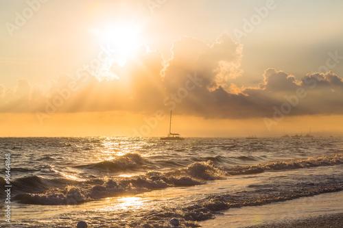 Foto op Canvas Zee zonsondergang Boat and golden sunrise over ocean in Dominican Republic