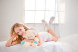 Woman lying on the bed with teddy bear