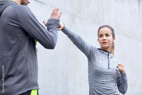 woman with coach working out strike outdoors Poster
