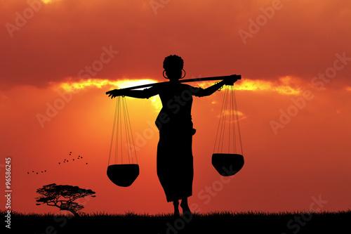 Foto op Canvas Baksteen African woman carrying water at sunset