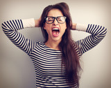 Angry young business woman in glasses strong screaming with wild