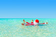 Santa Claus swimming in ocean water, Christmas concept