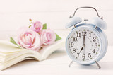 Fototapety Blue retro alarm clock with book and pink pastel roses
