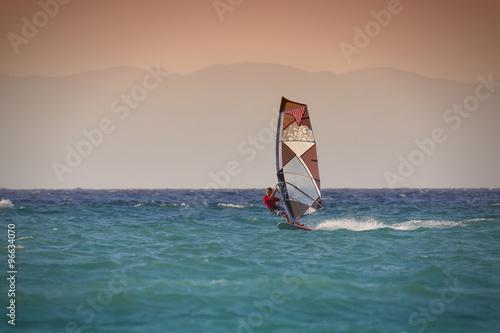obraz lub plakat Windsurfen in Rhodos Griechenland. Mann surft im blauen Meer vor rötlichem Himmel, Insel im Hintergrund.