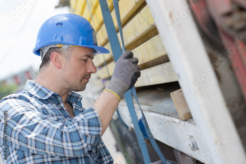 Poster Man securing straps to side of lorry
